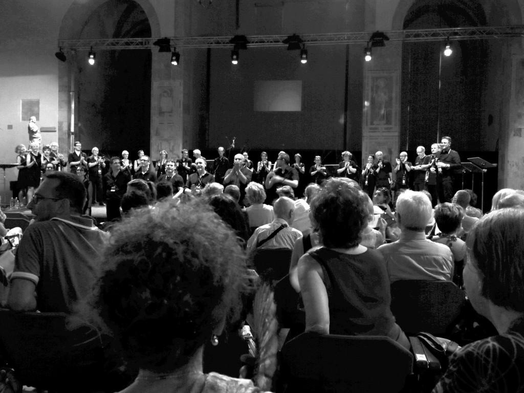 I Maestri ricevono l'applauso finale (solo una parte dei coristi è visibile perché distribuiti in tutta la chiesa)